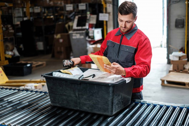 Warehouse worker sorting different packages